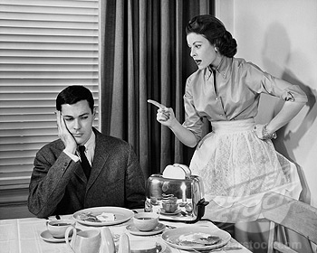 Woman scolding man at dining table