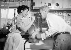 1950s HOUSEWIFE IN KITCHEN HAVING HUSBAND TASTE FOOD ON STOVE